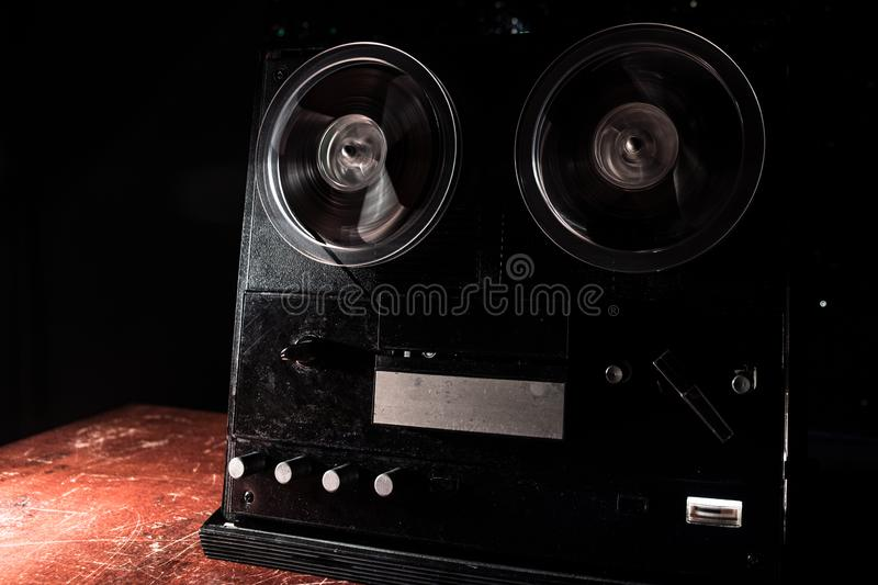 Special agent intelligence officer listens to conversations and records on a reel to reel tape recorder 3. Old vintage reel to reel player and recorder on dark stock photos