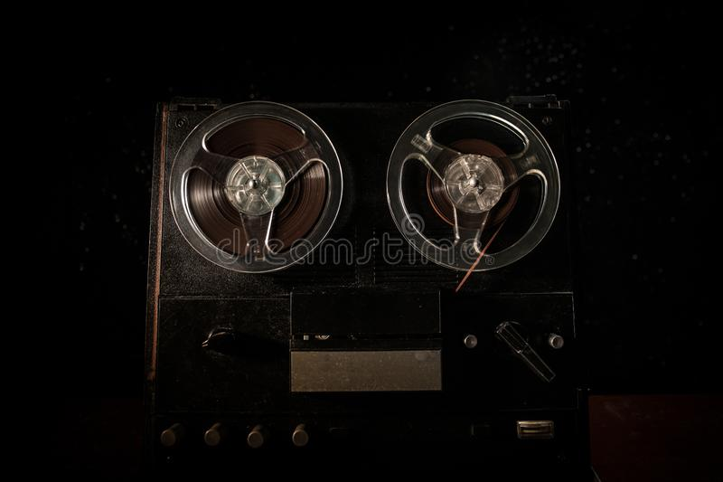 Special agent intelligence officer listens to conversations and records on a reel to reel tape recorder 3. Old vintage reel to reel player and recorder on dark stock image