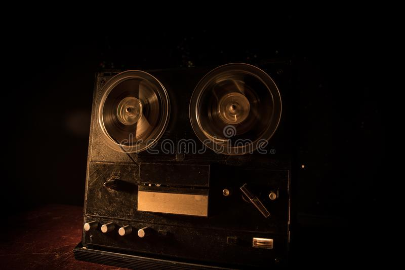 Special agent intelligence officer listens to conversations and records on a reel to reel tape recorder 3. Old vintage reel to reel player and recorder on dark stock photo
