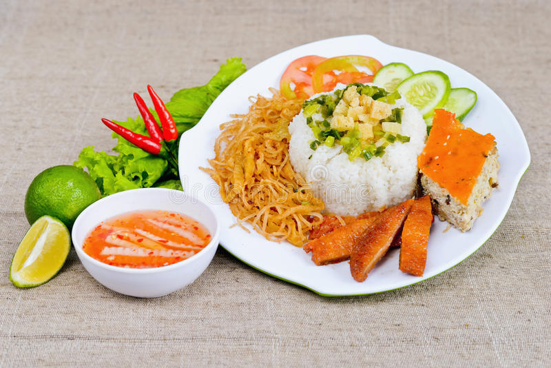 Special broken rice with fish sauce, lemon, fried pig skin, sliced cucumber and chili on white plate in Vietnam stock photos