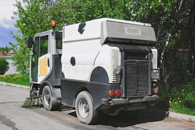 The special car cleans city road. Machine sweeper - cleaner cleans the roadway. Machine brushes sweeping the street. The car vacuumed on the street. Municipal stock image