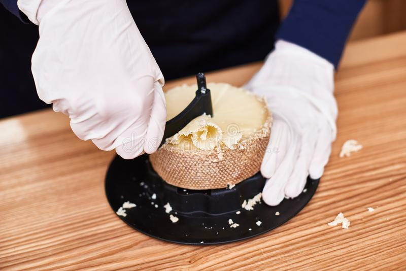 Special cheese knives. The scraper in cheese wheel. Cheese decoration. Woman cutting rosettes of Swiss monk cheese with traditional knife stock images