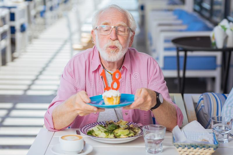 Positive aged man having a birthday party royalty free stock image