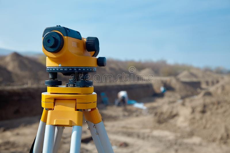 Special device level for surveyor builders, geodesy equipment close up in front of a ground work with people on blurred backgrou. Nd. Outdoors, copy space royalty free stock image