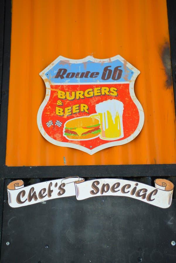 Special do ` s do sinal, dos hamburgueres e da cerveja fria, do cozinheiro chefe do vintage de Route 66, alimento e negócio das b fotografia de stock