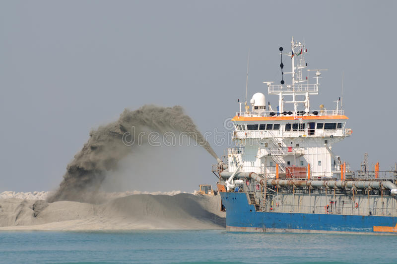 Special dredge ship. Pipe pushing sand to create new land in Dubai, United Arab Emirates royalty free stock images