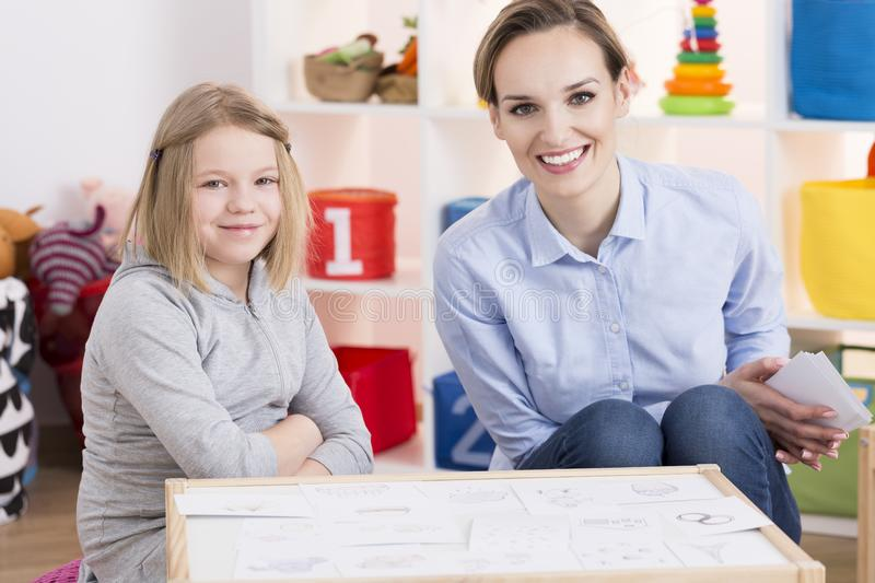 Special educator and child patient. Female special educator and child patient during therapy using pictures stock photography