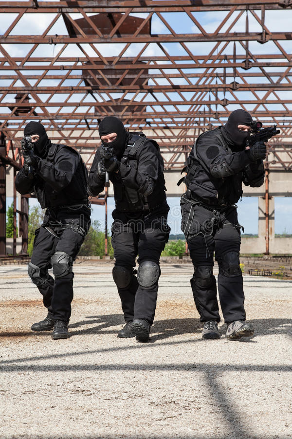 Special forces in action. Special forces operators in black uniform in action stock images