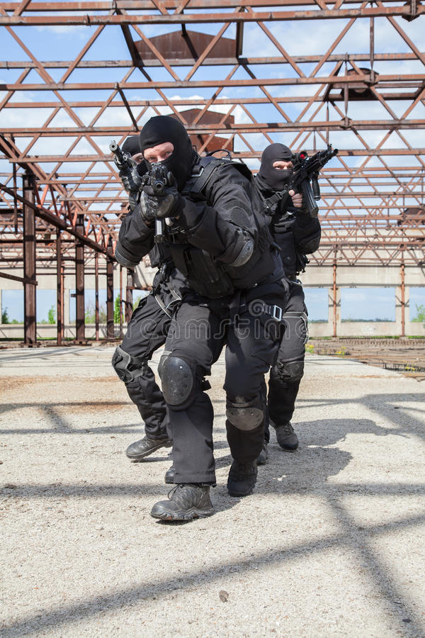 Special forces in action. Special forces operators in black uniform in action stock photos