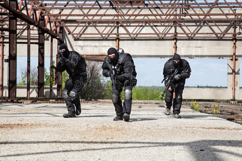 Special forces in action. Special forces operators in black uniform in action stock photography
