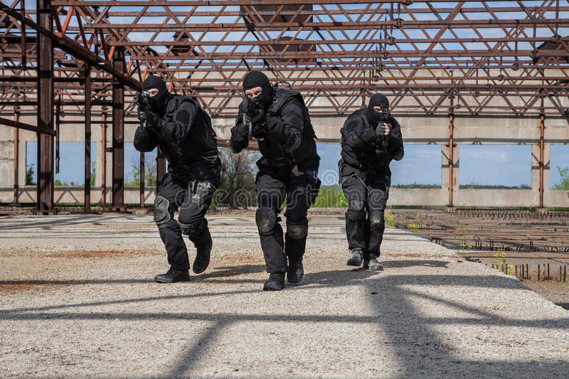 Special forces in action. Special forces operators in black uniform in action stock photo