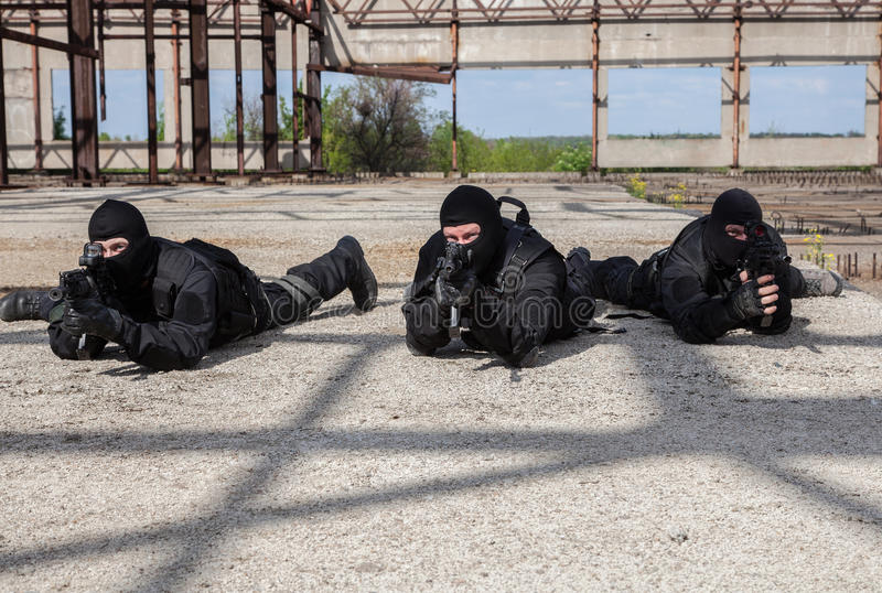 Special forces in action. Special forces operators in black uniform in action stock image