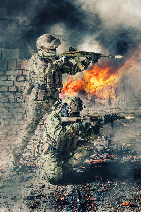 Special forces in action. Pair of special forces shooting a weapons. Brothers in arms in action. Guns blazing, ruined walls of buildings, explosions, gunfire and stock photography