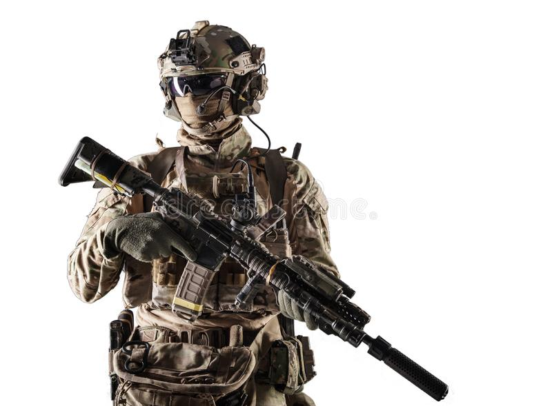 Modern army armed ranger isolated studio portrait. Special forces fighter in battle uniform and helmet with radio headset, face mask and ballistic glasses royalty free stock photography