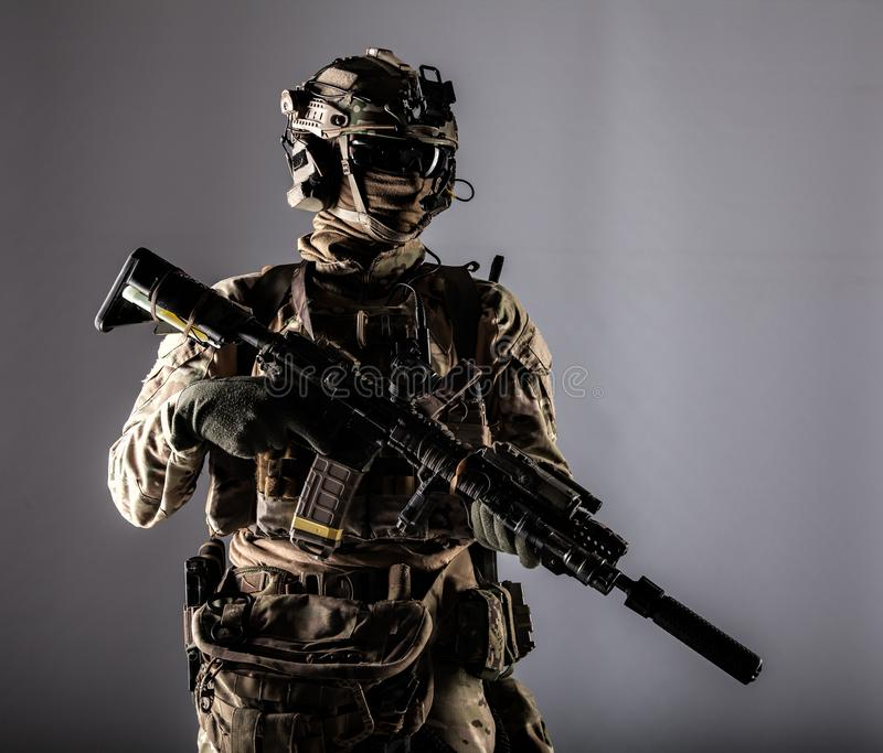 Modern army armed ranger isolated studio portrait. Special forces fighter in battle uniform and helmet with radio headset, face mask and ballistic glasses royalty free stock image