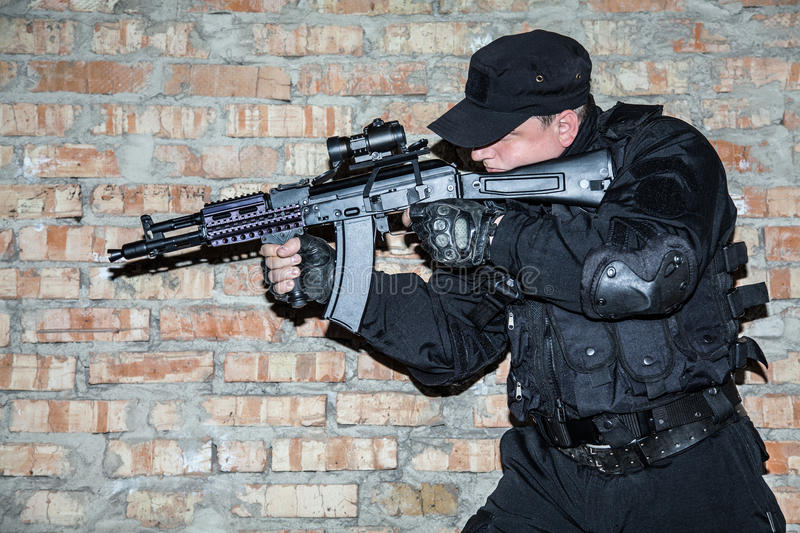 Special forces operator. In black uniform and bulletproof royalty free stock photography