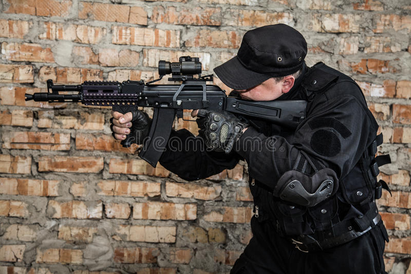 Special forces operator. In black uniform and bulletproof stock photo