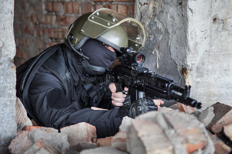Special forces operator. In black uniform and bulletproof stock images