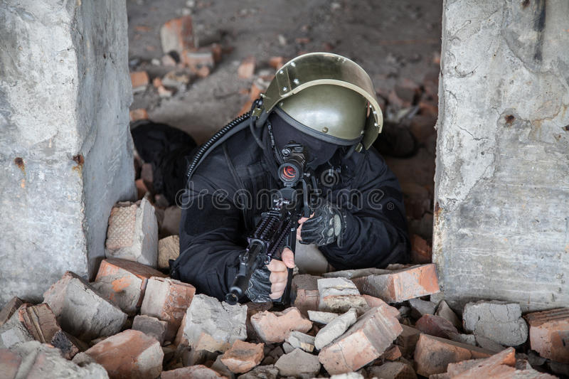 Special forces operator. In black uniform and bulletproof stock image