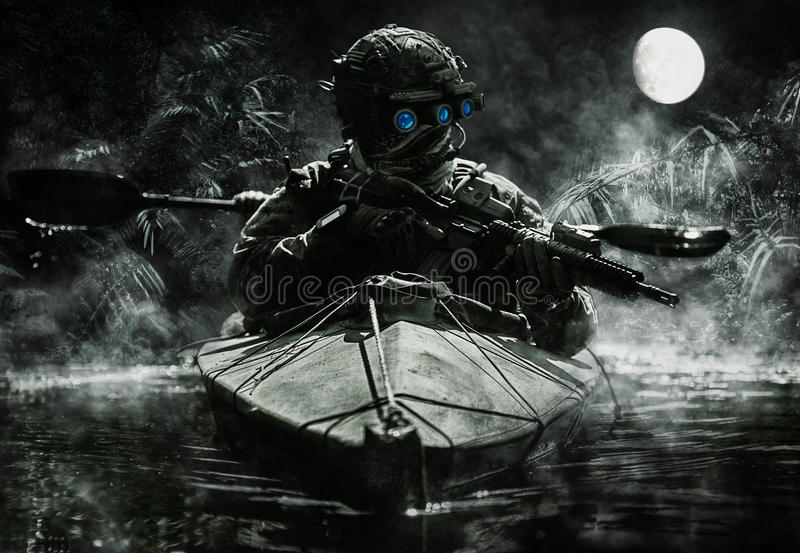 Special forces operators with night vision goggles. Two special forces operators with night vision goggles paddling in the army kayak in the jungle. Cloudy night stock photo