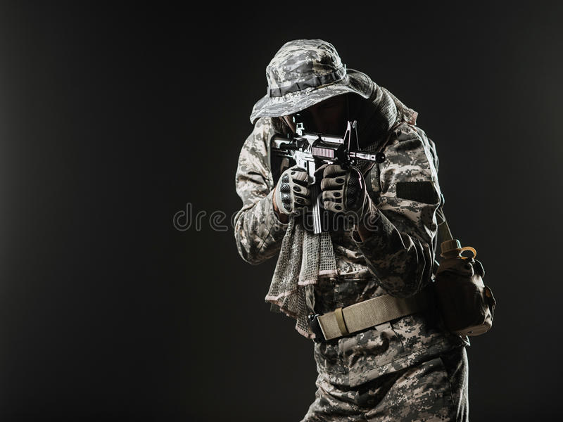 Special forces soldier man with Machine gun on a dark background. Military, war, conflict, soldiers - Special forces soldier man hold Machine gun on a dark stock photography