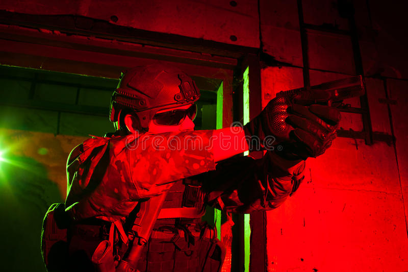 Special forces soldier during night mission. Special forces soldier or contractor during night mission/operation (red and green light for underline the royalty free stock image