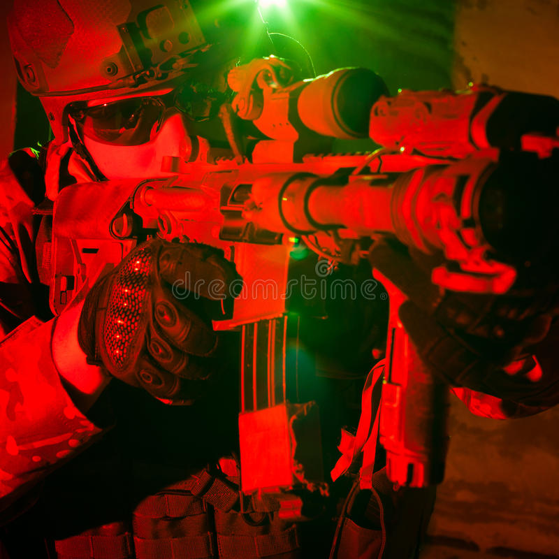 Special forces soldier during night mission. Special forces soldier or contractor during night mission/operation (red and green light for underline the stock photography