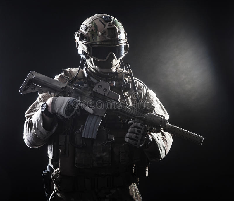 Special forces soldier. With rifle on dark background royalty free stock photography