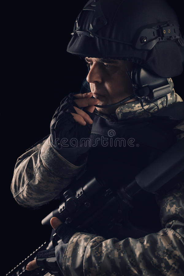 Special forces soldier with rifle on dark background stock images