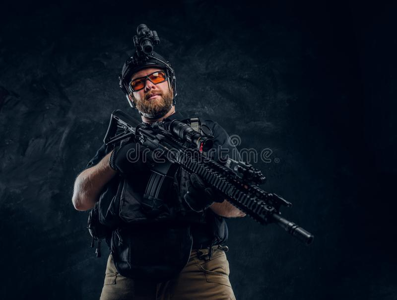 Special forces soldier wearing body armor and helmet with night vision holding an assault rifle. Studio photo against a royalty free stock image