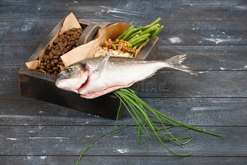 Special husdjurmat VS naturlig husdjurmat Ingredienskalkon, gryn, l?nef?rh?jning, gr?splaner och groddar i brun tr?ask arkivfoton