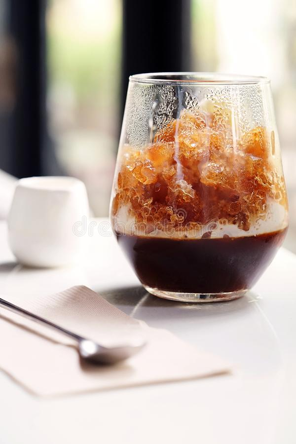 A special iced coffee menu served with coffee jelly in bottom and topped with crushed freezing milk in first layer stock photography