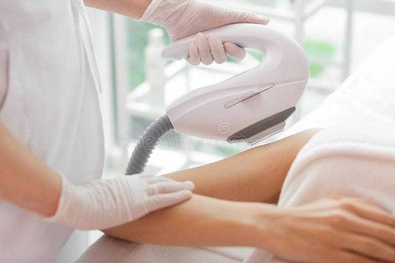 Special laser device used for tattoo removal. Aesthetic cosmetology. Special laser device being in used for tattoo removal in the beauty clinic stock images