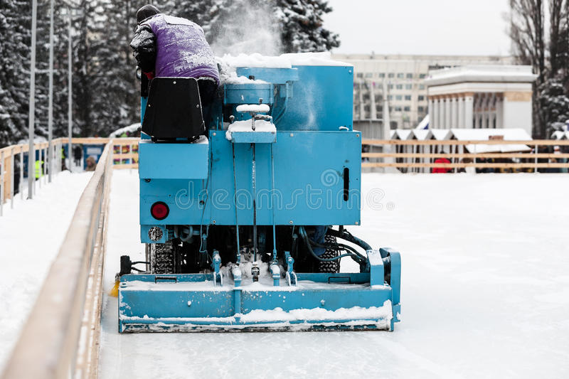 Special machine cleaning ice at ice skate rink. Special machine cleaning large amount of snow at ice skate rink.Winter holidays concept royalty free stock photo