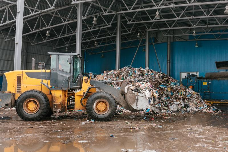 Special machinery or bulldozer work on the site of waste unloading at the plant for waste disposal. royalty free stock photography