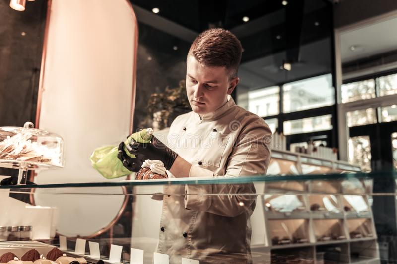 Serious smart confectioner holding a pastry bag royalty free stock photography