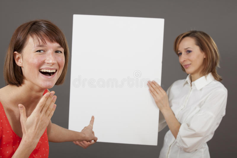 Special offer. Or great deal - happy women pointing with a finger on blank board stock photo