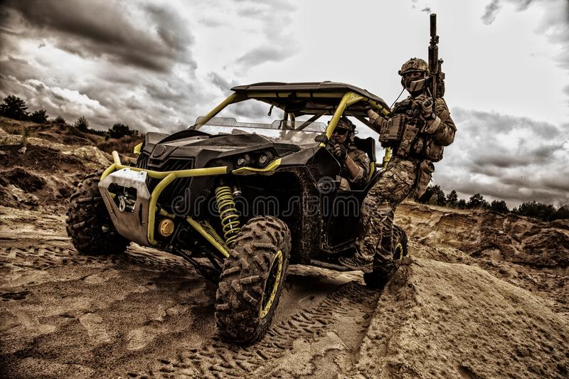 Commandos quick reaction combat group on buggy. Special operations forces fighters, commandos of quick reaction group armed service carbine moves on mobile royalty free stock photography