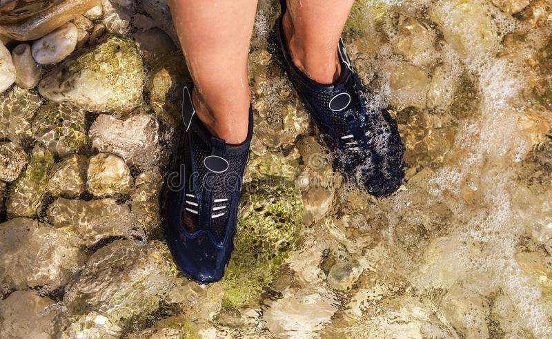 Special shoes for walking on the stones in the sea. Female feet close-up royalty free stock photos