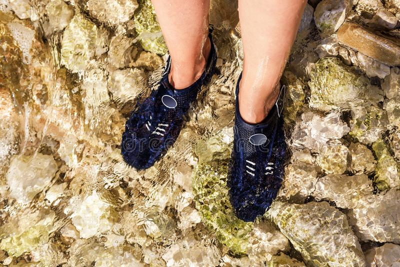 Special shoes for walking on the stones in the sea. Female feet close-up royalty free stock photography