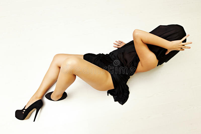 Special toned photo of female body in black silk fabric and in high heels shoes luing on floor royalty free stock photos