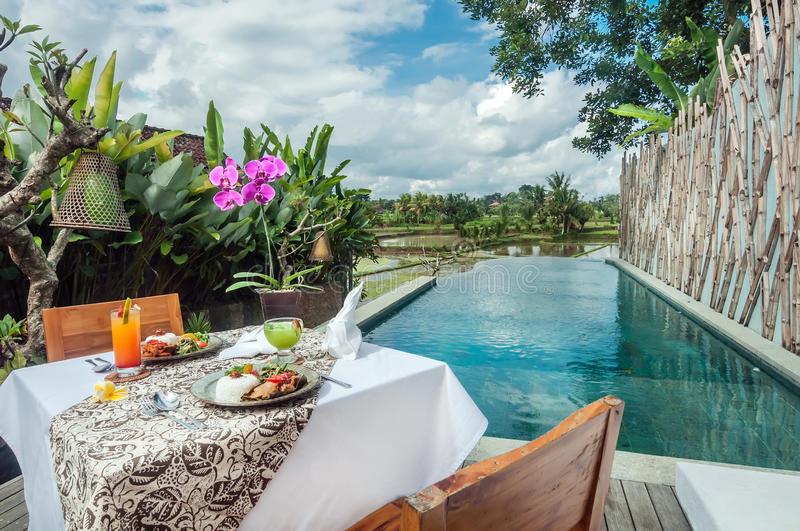 Special traditional lunch menu set on the table outdoor. Special lunch set on the table outdoor with Indonesian traditional food, pool area, overlooking to the royalty free stock photos