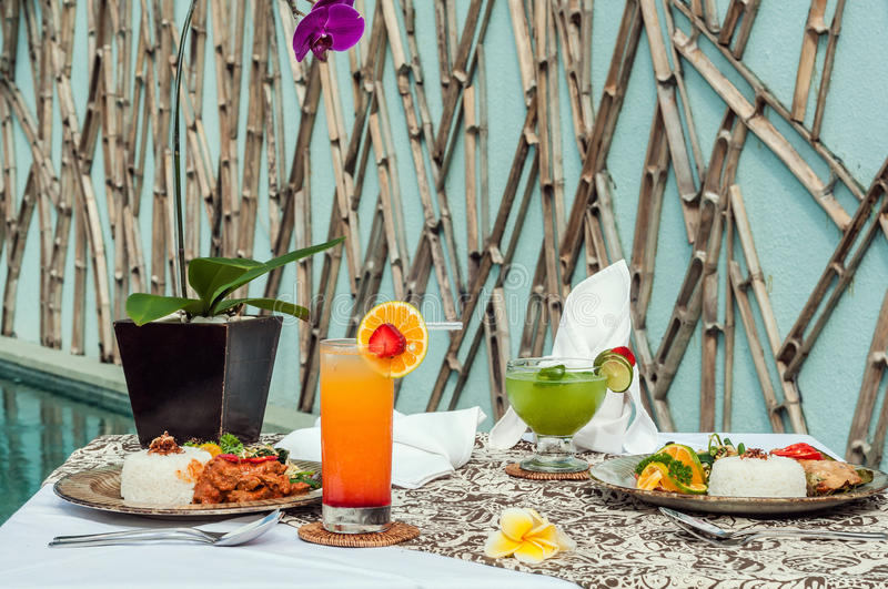 Special traditional lunch menu set on the table outdoor. Special lunch set on the table outdoor with Indonesian traditional food, pool area, overlooking to the stock images