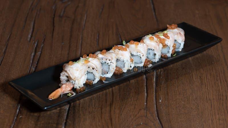 Special Uramaki with raw shrimp, sea bass, onions, Ikura, Ponzu sauce. Dark wood table background stock image