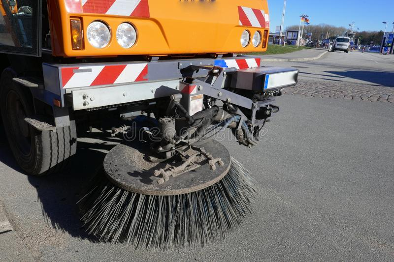 Special vehicle of the city cleaning sweeps the road with rotary brooms, close-up. Cleaning the streets, close-up royalty free stock image