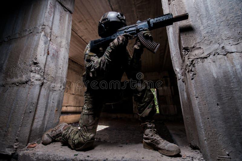 Speciale krachtenmilitair die een geweer in donkere ruimte streven stock afbeelding