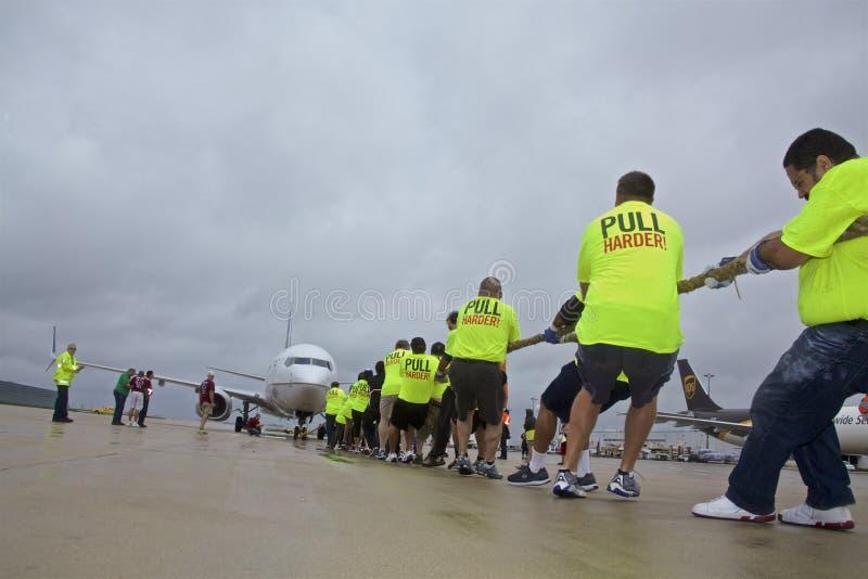 Speciale Olympics Team Pulls United Airplane in Regenachtig Chicago O& x27; Hazen Internationale Luchthaven royalty-vrije stock foto's