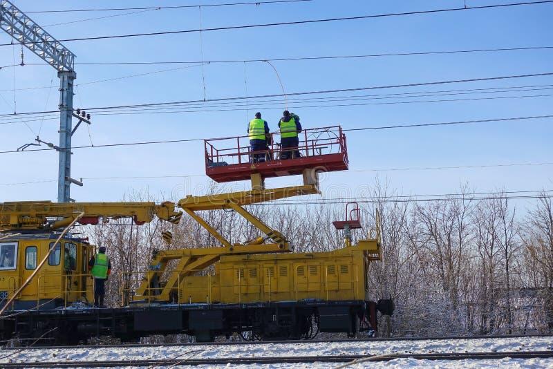 Speciale trein met een landende kraan voor de dienst en reparatie van elektronetwerken op de spoorweg Arbeiders die het de dienst royalty-vrije stock afbeeldingen