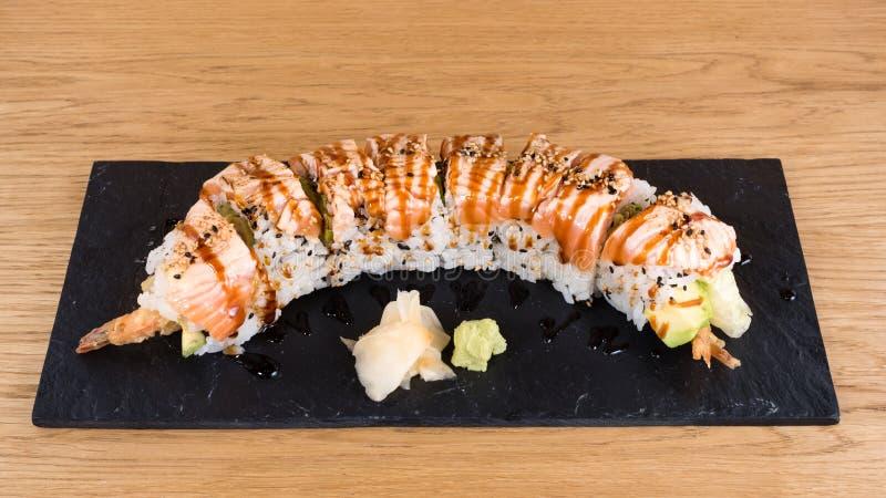 Speciale Uramaki, rotolo del riso farcito con la tempura del gamberetto, insalata verde, avocado, coperto di salmone arrostito, c fotografia stock libera da diritti