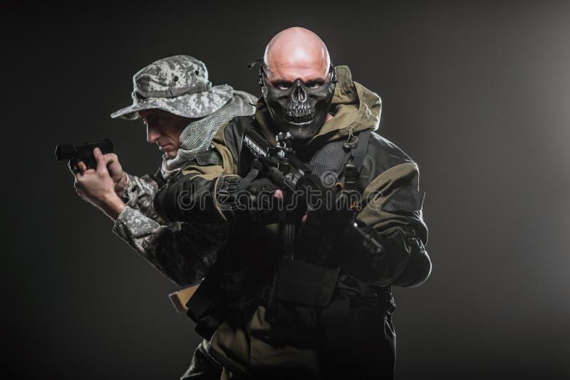 Specialförband tjäna som soldat män med maskingeväret på en mörk bakgrund arkivbild